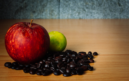 bad apple: Red Apple, Lime and Coffee bean on a wood with Dramatic Lighting, Selective focus, Vintage tone. Stock Photo