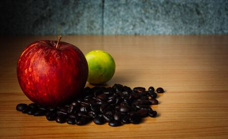 Red Apple, Lime and Coffee bean on a wood with Dramatic Lighting, Selective focus, Vintage tone. Banque d'images