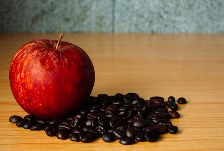 bad apple: Red Apple and Coffee bean on a wooden table with Dramatic lighting, Selective focus, Vintage tone