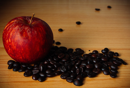 Red Apple and Coffee bean on a wooden table with Dramatic lighting, Selective focus, Vintage tone