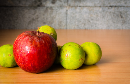 bad apple: Red Apple and Lime on a wooden table with Dramatic lighting, Selective focus.