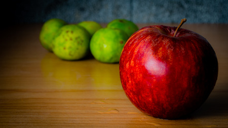 Red Apple and Lime on a wooden table with Dramatic lighting, Selective focus.
