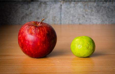 Pomme rouge et citron vert sur une table en bois avec éclairage dramatique, mise au point sélective. Banque d'images - 44275489