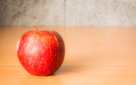 Red Apple on a wooden table with Dramatic lighting, Selective focus.