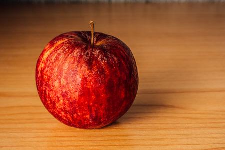 Pomme rouge sur une table en bois avec éclairage dramatique, mise au point sélective. Banque d'images - 44276632