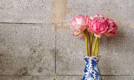 lighting background: Bouquet of Pink Lotus on dark brick background, Dramatic lighting, Selective focus. Stock Photo