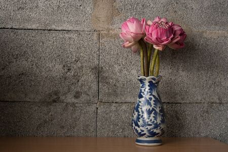 Bouquet of Pink Lotus on dark brick background, Dramatic lighting, Selective focus. Banque d'images
