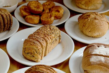 Baked bread on white plate and wooden table with Selective focus.