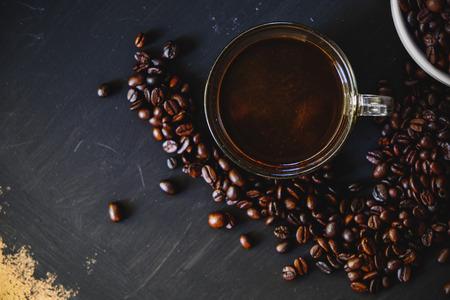 Grains de café torréfiés dans une tasse blanche avec une boisson chaude espresso sur fond sombre. Low key, ton Vintage, d'en haut Banque d'images - 66331973