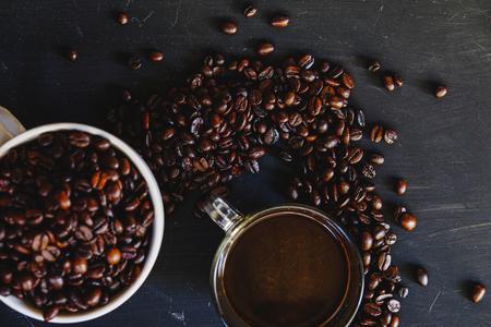 Grains de café torréfiés dans une tasse blanche avec une boisson chaude espresso sur fond sombre. Low key, ton Vintage, d'en haut Banque d'images - 66332086