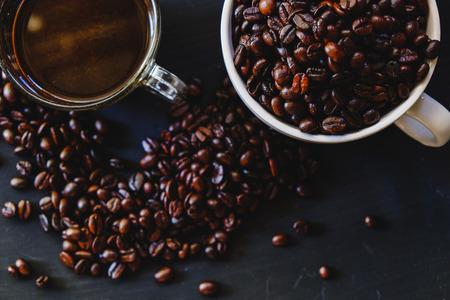 Grains de café torréfiés dans une tasse blanche avec une boisson chaude espresso sur fond sombre. Low key, ton Vintage, d'en haut Banque d'images - 66284950
