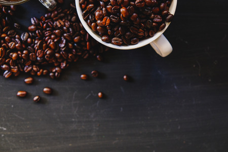Roasted coffee bean in white cup with hot espresso drink on dark background. Low key, Vintage tone, From above Banque d'images