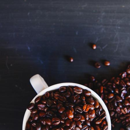Grains de café torréfiés dans une tasse blanche avec une boisson chaude espresso sur fond sombre. Low key, ton Vintage, d'en haut Banque d'images - 66284960