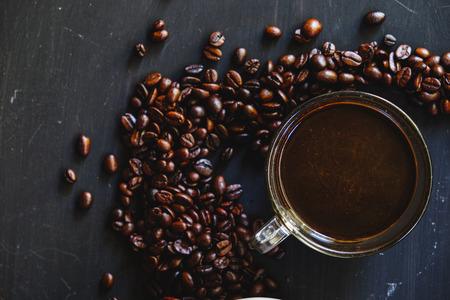 Grains de café torréfiés dans une tasse blanche avec une boisson chaude espresso sur fond sombre. Low key, ton Vintage, d'en haut Banque d'images - 66284961