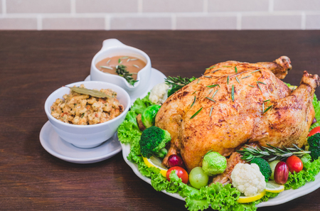 Roasted turkey stuffing garnished with Vegetables served with gravy sauce on a rustic style table. Christmas Dinner Stock Photo