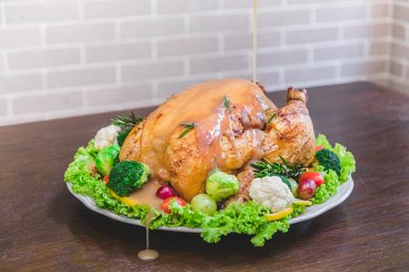 Geroosterde kalkoen vulling gegarneerd met groenten geserveerd met jus saus op een rustieke stijl tafel. Kerstdiner Stockfoto
