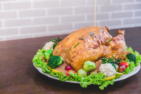 Roasted turkey stuffing garnished with Vegetables served with gravy sauce on a rustic style table. Christmas Dinner 免版税图像