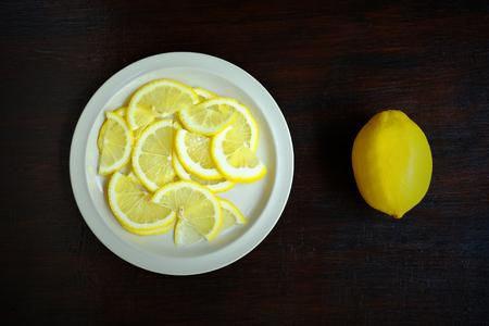 Luchtmening van gesneden citroen in een witte schotel op een houten lijst, het beeld van het Voedselingrediënt