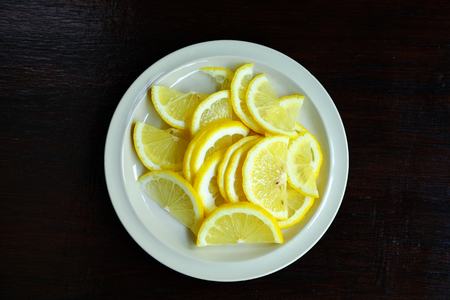 Overhead view of sliced lemon in a white dish on a wooden table, Food ingredient image