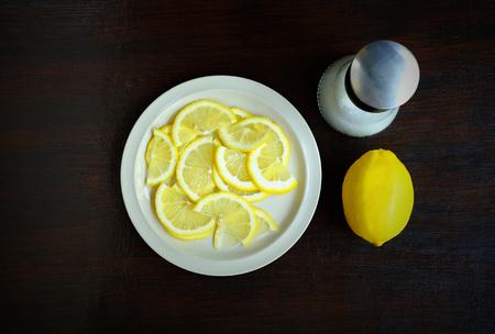 Luchtmening van gesneden citroen in een witte schotel met zoute schudbeker op een houten lijst, het beeld van het Voedselingrediënt