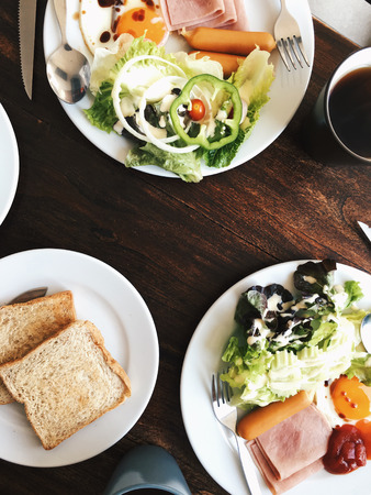 plato del buen comer: Overhead view of Hotel Breakfast - Soft boiled rice with fried eggs, bacon, sausages, ham, fresh salad, toast and hot tea on top a wooden table