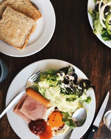 Vue aérienne de l'Hôtel Petit-déjeuner - Soft riz bouilli avec des ?ufs frits, bacon, saucisses, jambon, salade fraîche, du pain grillé et du thé chaud sur le dessus d'une table en bois Banque d'images - 67099277
