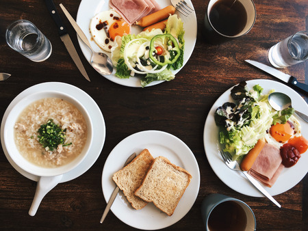Vue aérienne de l'Hôtel Petit-déjeuner - Soft riz bouilli avec des ?ufs frits, bacon, saucisses, jambon, salade fraîche, du pain grillé et du thé chaud sur le dessus d'une table en bois Banque d'images - 66938550