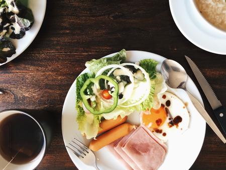 Vue aérienne de l'Hôtel Petit-déjeuner - Soft riz bouilli avec des ?ufs frits, bacon, saucisses, jambon, salade fraîche, du pain grillé et du thé chaud sur le dessus d'une table en bois Banque d'images - 67051138