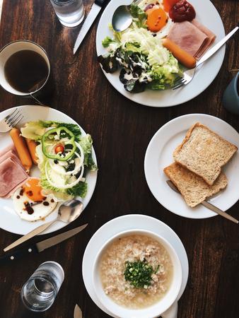 Vue aérienne de l'Hôtel Petit-déjeuner - Soft riz bouilli avec des ?ufs frits, bacon, saucisses, jambon, salade fraîche, du pain grillé et du thé chaud sur le dessus d'une table en bois Banque d'images - 67089933