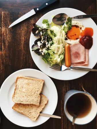 Vue aérienne de l'Hôtel Petit-déjeuner - Soft riz bouilli avec des ?ufs frits, bacon, saucisses, jambon, salade fraîche, du pain grillé et du thé chaud sur le dessus d'une table en bois Banque d'images - 67068592