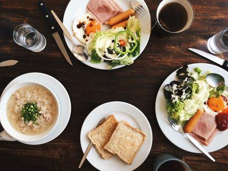Vue aérienne de l'Hôtel Petit-déjeuner - Soft riz bouilli avec des ?ufs frits, bacon, saucisses, jambon, salade fraîche, du pain grillé et du thé chaud sur le dessus d'une table en bois Banque d'images - 67051146