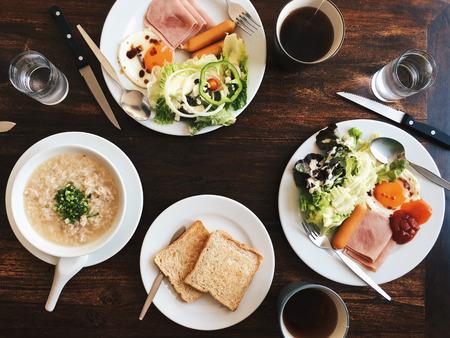 Bovenaanzicht van Hotel ontbijt - zacht gekookte rijst met gebakken eieren, spek, worst, ham, verse salade, toast en warme thee op de top van een houten tafel