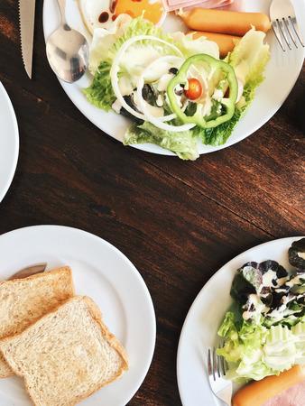 Vue aérienne de l'Hôtel Petit-déjeuner - Soft riz bouilli avec des ?ufs frits, bacon, saucisses, jambon, salade fraîche, du pain grillé et du thé chaud sur le dessus d'une table en bois Banque d'images - 67051158