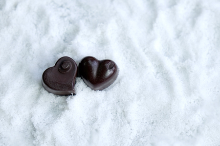 Assorted milk and dark chocolate heart on snow with copy space, Black Valentine's Day concept. Banque d'images - 123544752