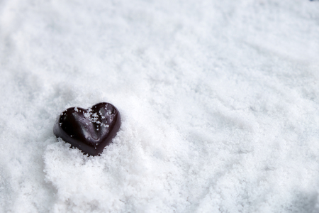 Assorted milk and dark chocolate heart on snow with copy space, Black Valentine's Day concept. Banque d'images - 123544757