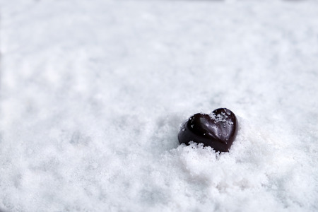 Assorted milk and dark chocolate heart on snow with copy space, Black Valentine's Day concept.