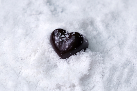 Assorted milk and dark chocolate heart on snow with copy space, Black Valentine's Day concept. Banque d'images - 123545274