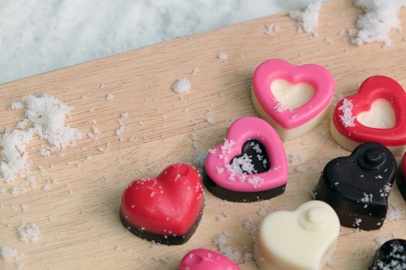Colorful milk chocolates heart on wooden plate and snow, Valentine's day concept.