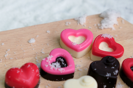 Colorful milk chocolates heart on wooden plate and snow, Valentine's day concept. Banque d'images - 123545288