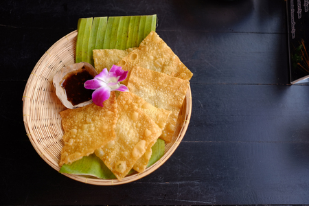 Crispy wonton. Fried wonton sheets in basket serve with Thai style chilli sauce in resturant.
