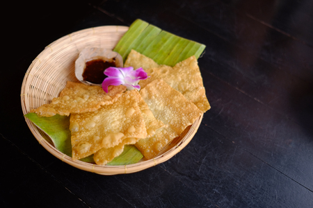 Crispy wonton. Fried wonton sheets in basket serve with Thai style chilli sauce in resturant. Banque d'images - 123549479