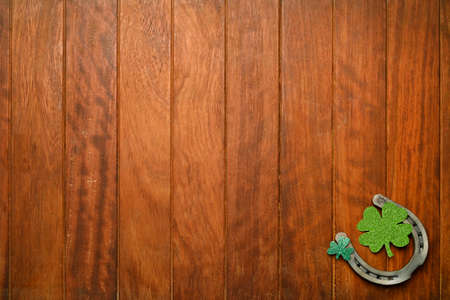 Concept of St. Patrick. green clovers, horseshoes coins on wooden background, top view place for text