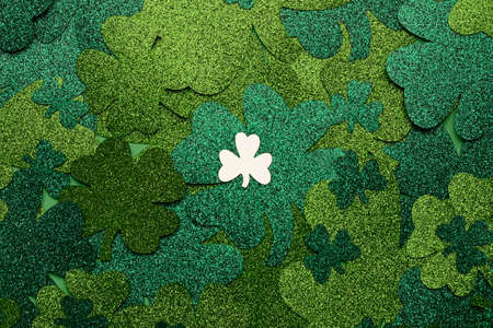 Concept of St. Patrick. A lot green clovers and one white clover, top view place for text