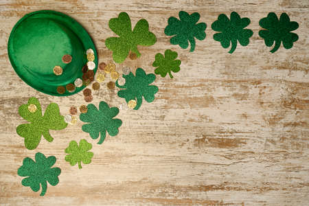 St. Patrick's concept. Green hat, shamrocks and lucky coins on wood background. top view place for text