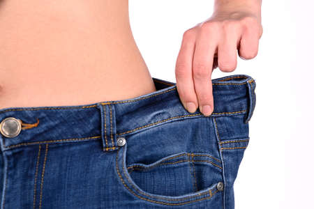Diet concept and weight loss. Young slim woman, in oversize jeans, measuring her waist on white background