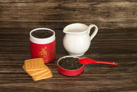 tea and biscuits: Tea, biscuits and a jar on a wooden background.