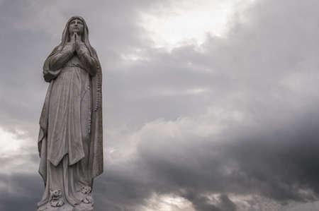 vierge marie: Statue de la Vierge Marie avec fond de ciel gris Banque d'images