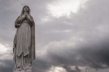 virgin mary: Statue of Virgin Mary with grey sky background Stock Photo
