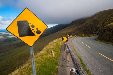 falling rocks Warning sign on a curvy road photo