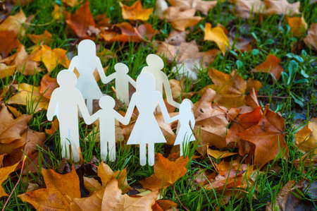 Paper family cut outs on autumn leaves Reklamní fotografie